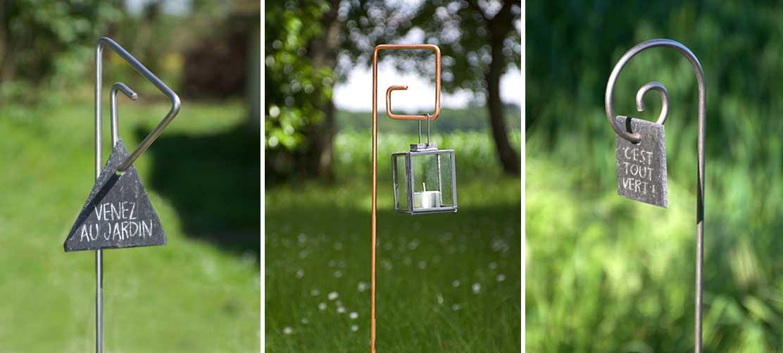 tuteur Pablo en fer diamètre 6mm avec une étiquette ardoise triangle, un tuteur Piet en cuivre avec une lanterne, un tuteur Gustav en inox diamètre 6mm avec une étiquette ardoise carrée.
